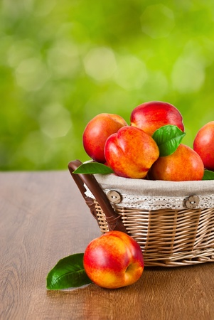 Fresh fruit nectarines in the basket with natural background Stock Photo
