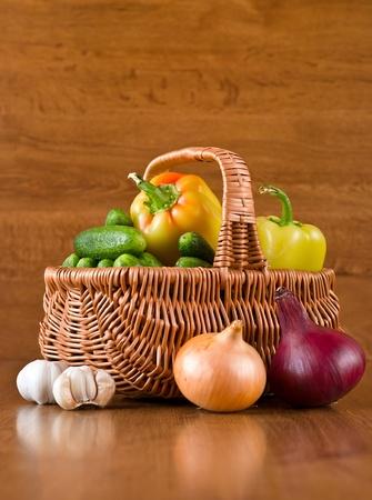 Fresh vegetables in basket on wooden background photo