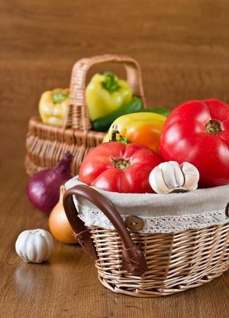 Harvest of fresh vegetables in baskets on wooden background photo