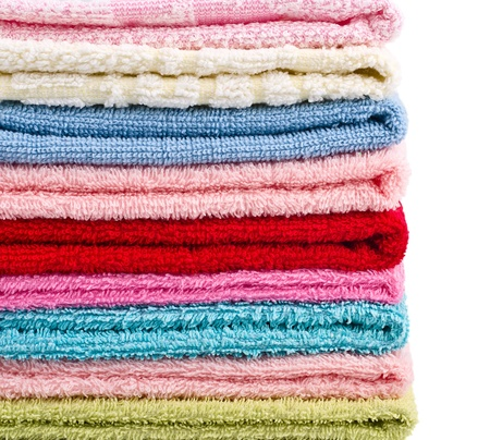 Pile stacked colorful towels isolated on white background