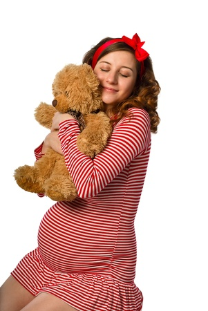 beautiful pregnant girl hugging a toy, isolated on white background
