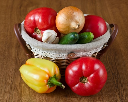 Harvest of fresh vegetables in baskets on wooden background photo