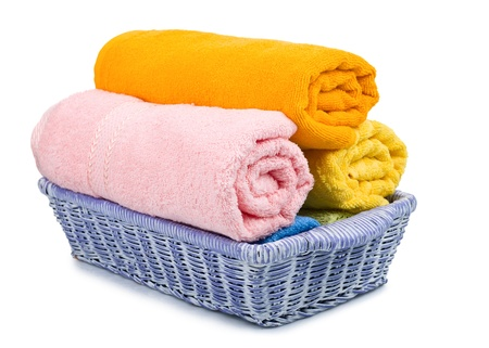 Multicolour towels rolls in basket on white background