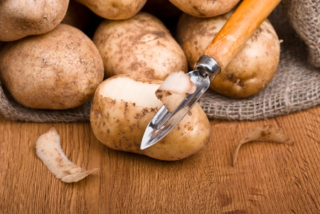 Fresh potatoes is peeled with a kitchen knife on the natural background Stock Photo