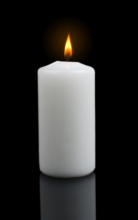 Closeup of burning candle isolated on black background  photo