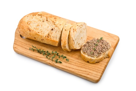 Slice of homemade bread with pate and herbs on a wooden cutting board isolated on white background