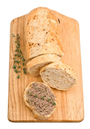 Slice of homemade bread with pate and herbs on a wooden cutting board isolated on white background photo