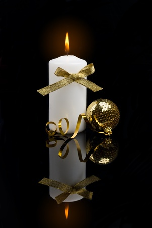 Christmas candle table setting with gold baubles bow and ribbon over black background photo
