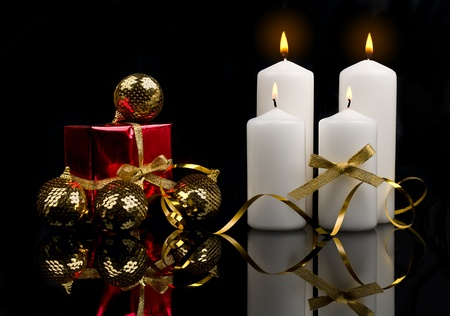 Christmas candles table setting with gold baubles bow and ribbon over black background Stock Photo - 11967725
