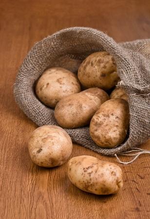 Harvest potatoes in burlap sack on rustic background Stock Photo
