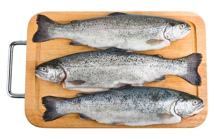 Three trout fish on wooden board, isolated on the white background  photo