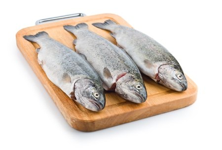 Three trout fish on wooden board, isolated on the white background