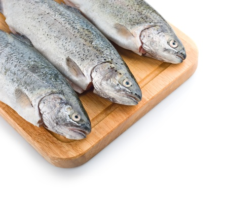 Three trout fish on wooden board, isolated on the white background Stock Photo - 13787083