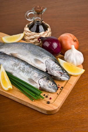 Fresh raw fish trout with peppers, onions and lemon on a wooden board