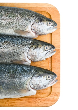Three trout fish on wooden board, isolated on the white background Stock Photo - 14125032