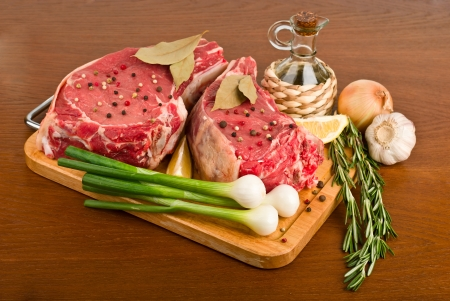 raw meat with rosemary, onion, garlic, peppercorn, lemon and oil