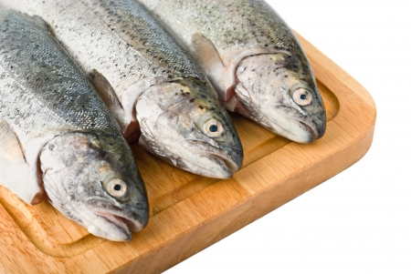 Three trout fish on wooden board, isolated on the white background Stock Photo - 14268659
