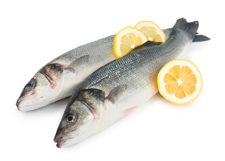 Two sea bass with lemon isolated on white background photo