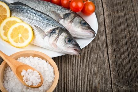 Sea Bass with salt and lemon on wood background