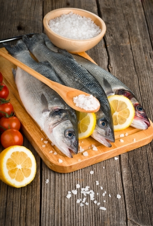 Sea Bass with salt and vegetables on wood background  photo