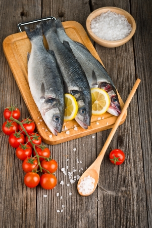 Sea Bass with salt, tomatoes and lemon, on wooden background Stock Photo