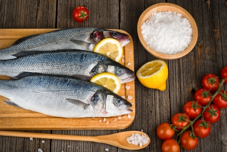 Fish sea bass with salt, lemon on wooden hardboard, prepared for cooking Stock Photo - 19742695