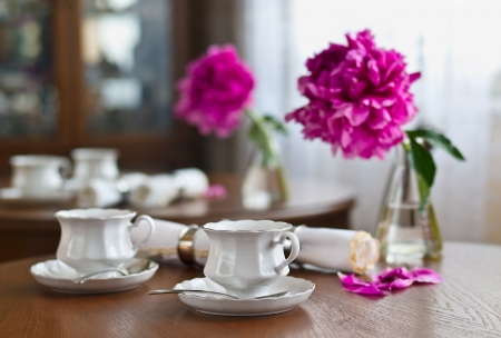 A cup of tea and napkin and peony on wooden table