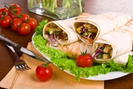 image of a doner kebab on white plate with vegetables Stock Photo