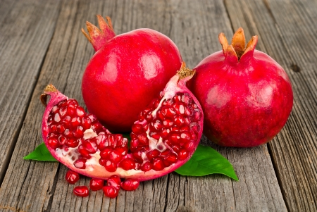 Fresh ripe pomegranates with leaves on an old wooden board Stock Photo