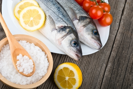 Steamed seabass with salt, lemon and tomato on wooden background