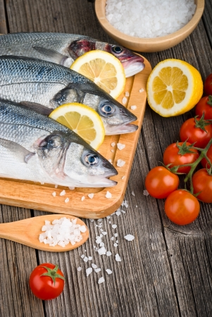 Fresh sea bass on chopping board with lemon and vegetables on wooden table