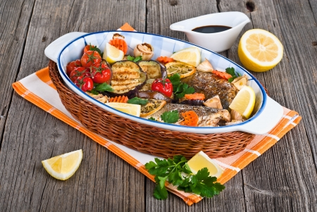 seabass fish baked with vegetables, herbs and lemon on a dish