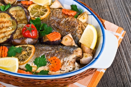 seabass fish baked with vegetables, herbs and lemon, close-up photo