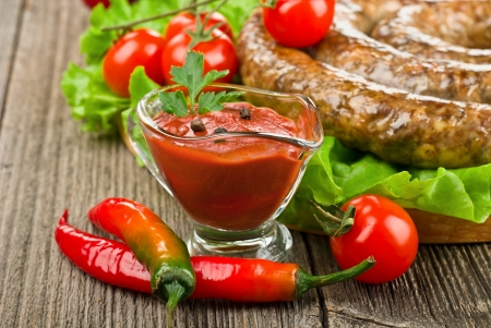 tomato sauce with Grilled sausage (kielbasa) ring on wooden board with vegetables, close-up Stock Photo