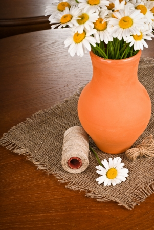 Beautiful bouquet of Chamomile flowers in clay pot on wooden table photo