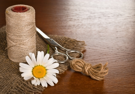 Scissors, cord and daisy flower on a wooden background photo