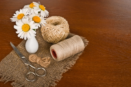 Scissors, cord and daisy flower in vase on a wooden background photo