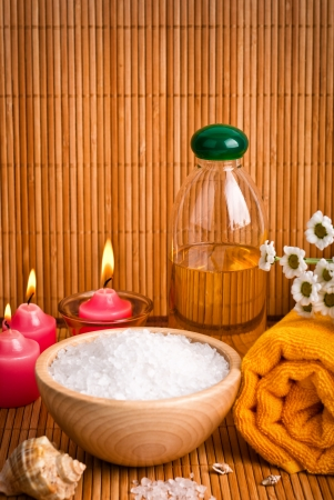 Spa still life with aromatic candles, Chamomile flower and towel photo