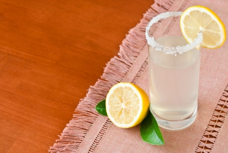 Refreshing lemonade in a glass on wooden table with space for text Stock Photo