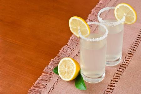 Two Glasses of fresh homemade tasty lemonade on wooden table