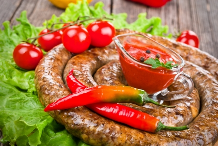 Sausage with tomatoes and hot peppers on wooden background