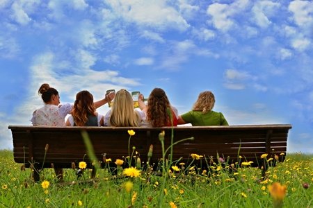 five girls sitting on a bench