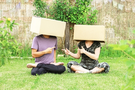 Couple with cardboard boxes over the head