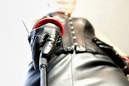 mistress with black leather outfit and whip 写真素材