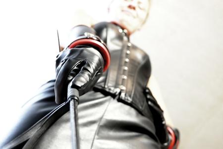 maîtresse avec tenue en cuir noir et fouet