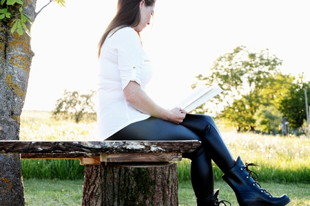 young women reads book on a wooden bench