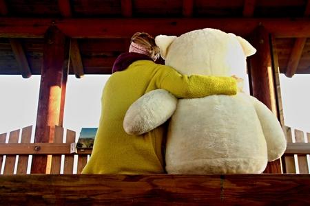 blonde young woman hugs huge teddy bear
