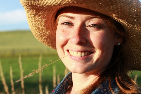 young cowgirl with blade of grass in mouth