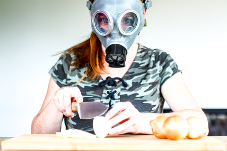 young women with gas mask cuts a onion