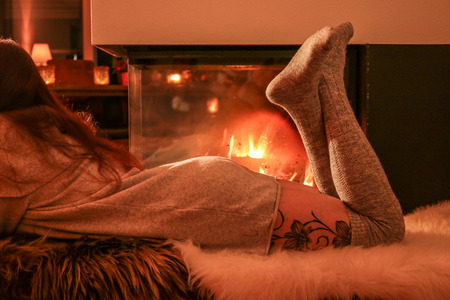 young woman is sitting by the fireplace Фото со стока